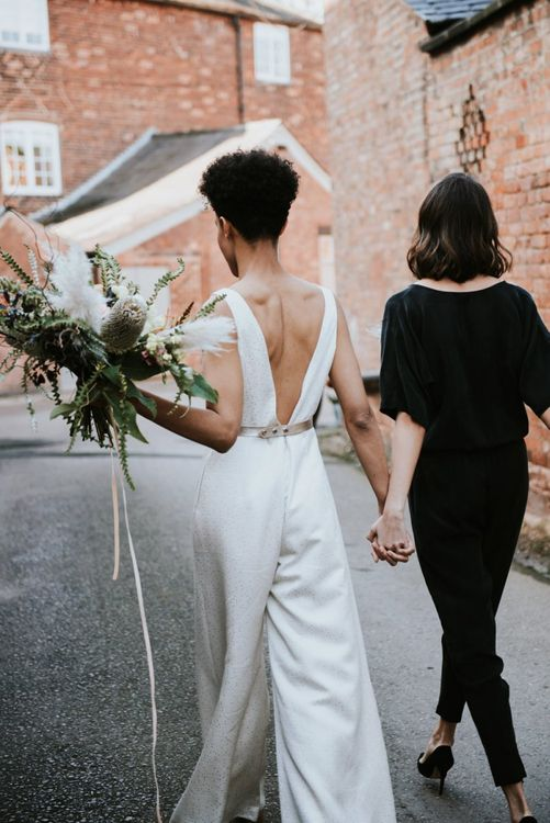 Two brides in black and white wedding jump-suits at industrial wedding venue