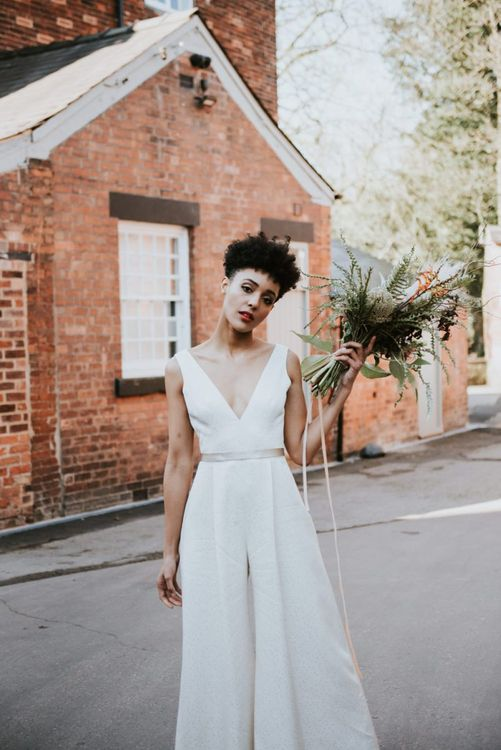 Stylish bride with short curly hair in a white wedding jumpsuit