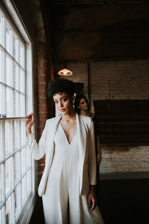 Stylish bride in wedding jumpsuit and blazer at The West Mill wedding venue