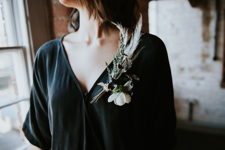 Bride in black jumpsuit with anemone buttonhole