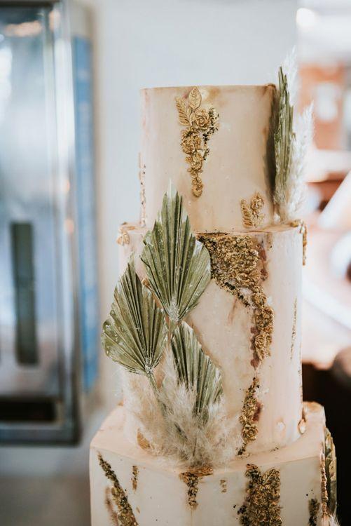Gold geode wedding cake with dried palm leaf decor