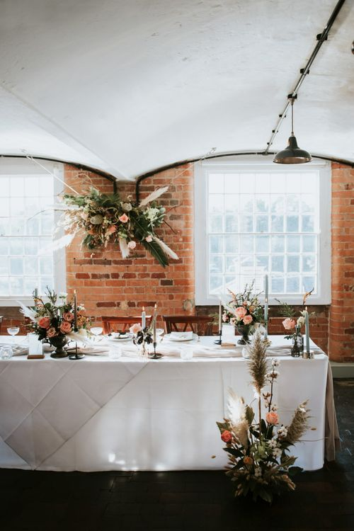 Top table at The West Mill with flower installation and centrepieces
