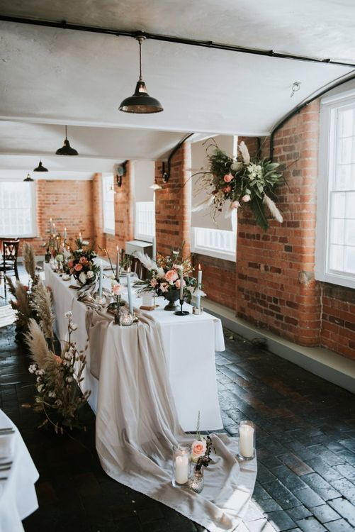 Elegant top table wedding decor with taper candles, floral arrangements and floral installation