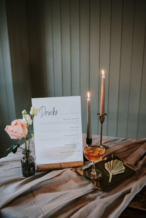 Drinks menu with taper candles and floral decor at The West Mill