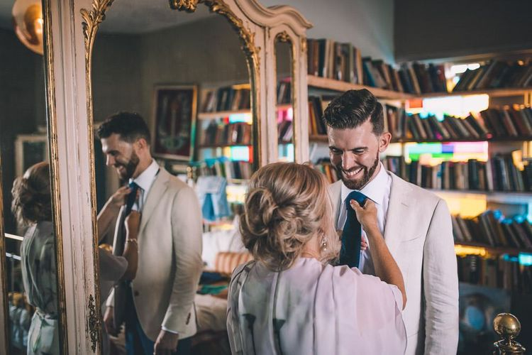 Groom getting ready for same-sex intimate city celebration in East London  wearing a white blazer