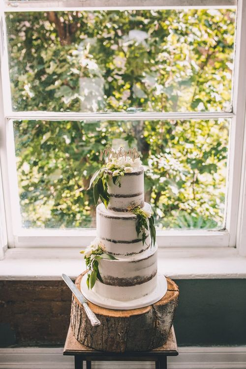 Semi-naked cake with white floral decoration on a tree trunk stand