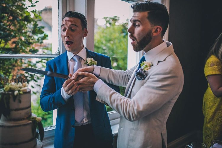 Grooms cut the semi-naked cake for intimate gay wedding in London