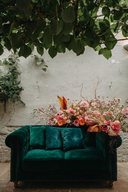 Green velvet sofa and pink wedding flowers at Secret Garden Kent