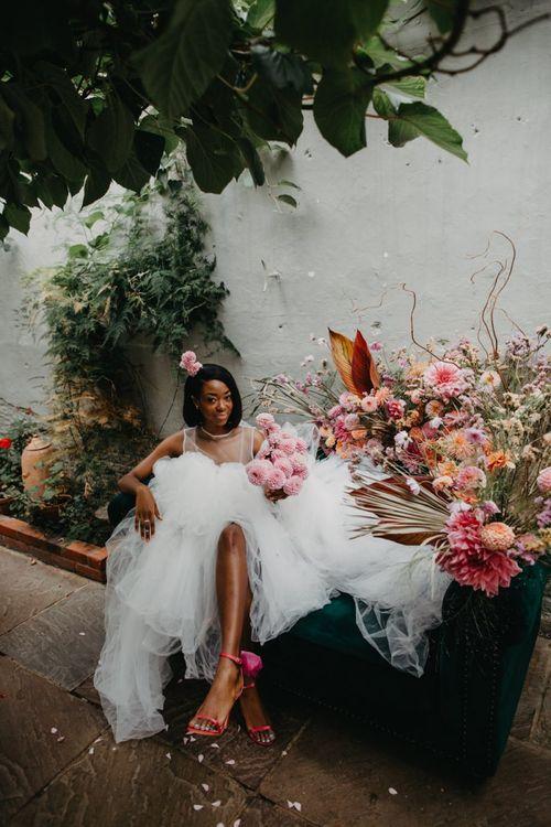 Bride in tulle wedding dress sitting on a flower filled sofa at Secret Garden Kent