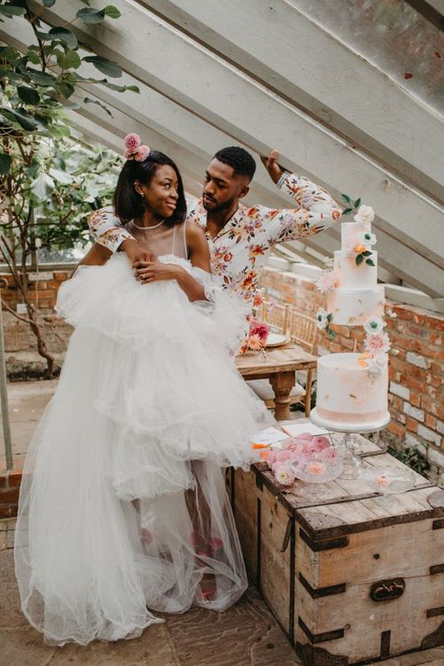 Bride in tulle wedding dress and groom in floral shirt cutting the wedding cake at tropical wedding