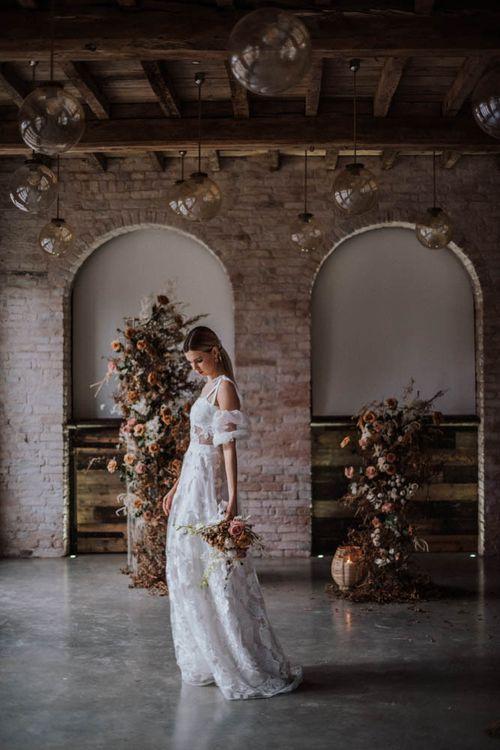 Bride in applique Emma Beaumont wedding dress standing in Iscoyd Park Coachhouse