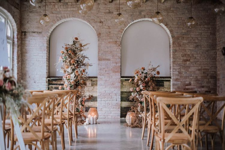 Ceremony setup at Iscoyd Park Coachhouse with wooden chairs and floral arrangements