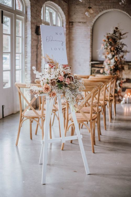 Wedding ceremony sign on white easel with orange flowers