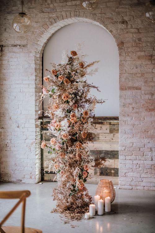 Vertical wedding flower arrangement with orange flowers and foliage