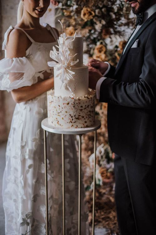 Bride and groom cutting the stylish wedding cake by Union Cakes