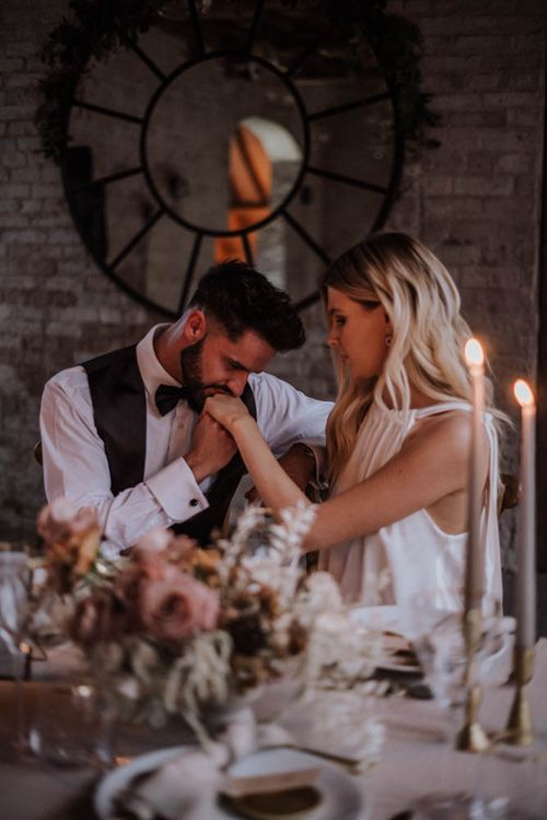 Groom kissing his brides hand at romantic, Iscoyd Park, wedding reception