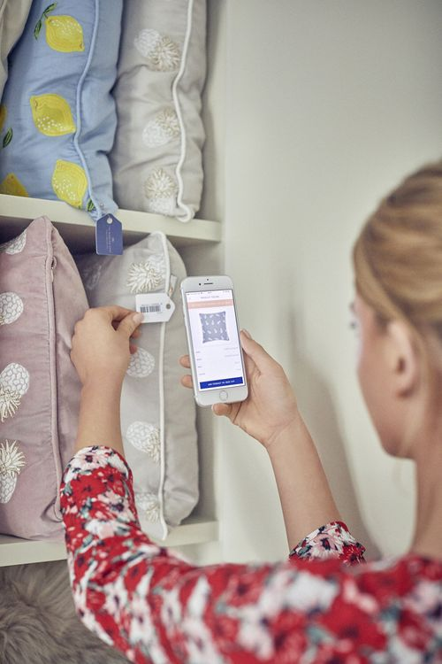 Bride-to-be scanning a cushion with their phone at The Wedding Shop London Townhouse