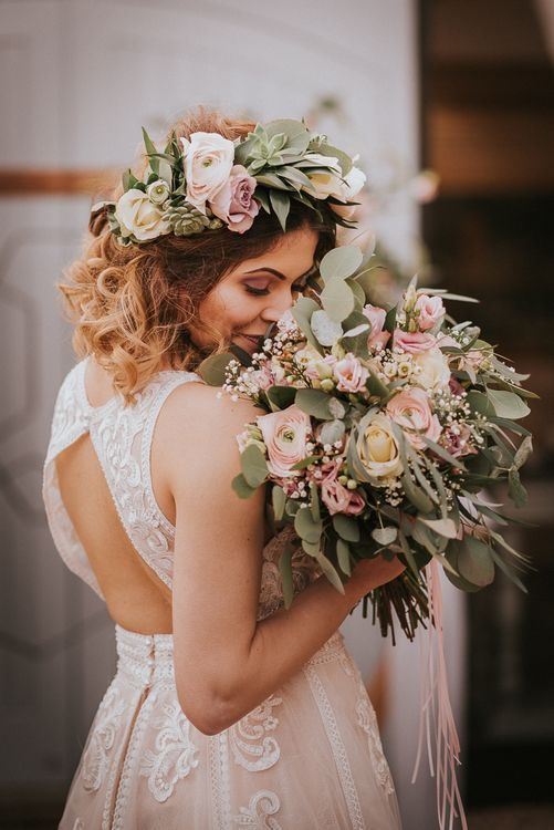 Bride in Lace Keyhole Back Wedding Dress Holding a Blush Pink,  White Rose and Foliage Wedding Bouquet
