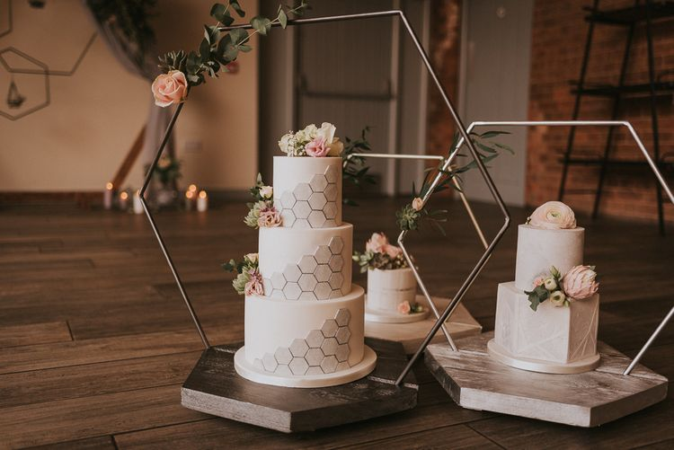 Three Individual Wedding Cakes with Silver Details on Hexagonal Stands