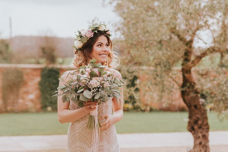 Boho Bride in Lace Wedding Dress and  Flower Crown Holding a Bridal Bouquet with Pink and White Roses