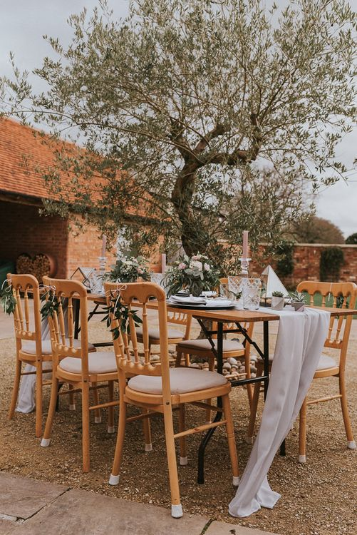 Outdoor Tablescape Under an Olive Tree with Linen Table Runner, Taper Candles, Cut Glass and Romantic Flower Arrangements