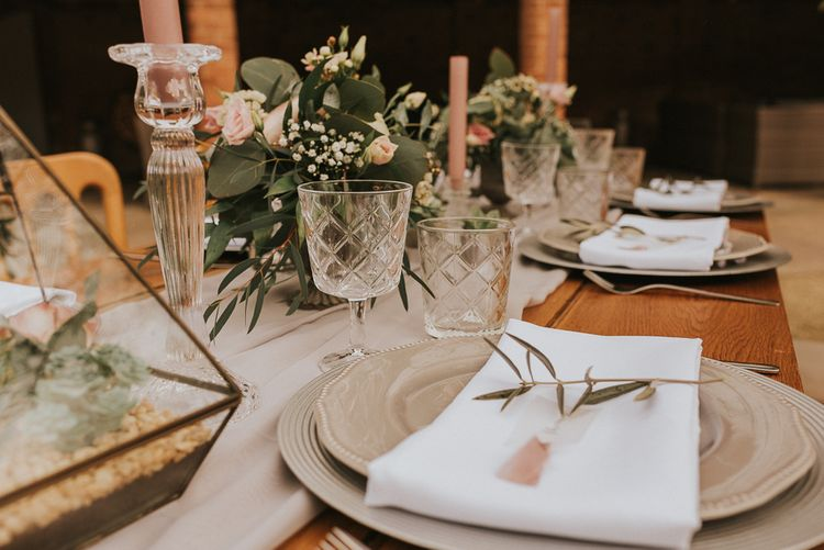 Elegant Place Setting with Grey Table Ware, White Napkin and Olive Branch