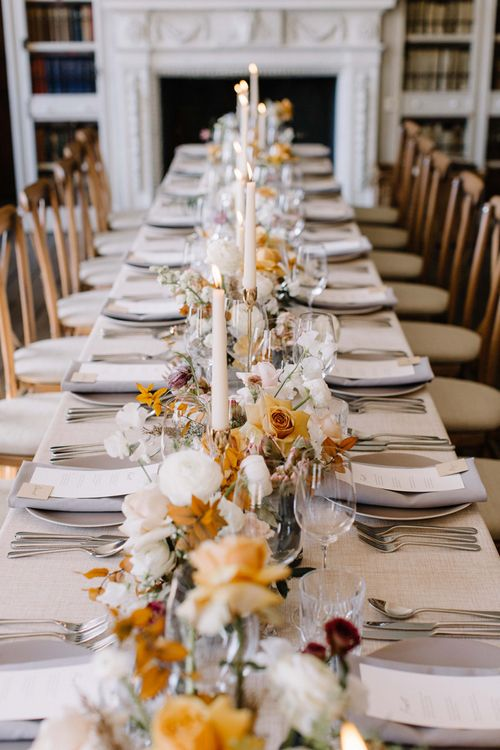 Muted Flowers and White Taper Candles Wedding Breakfast Table Centrepiece Decor