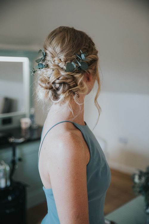 Bridesmaid with eucalyptus in braided, pinned wedding updo