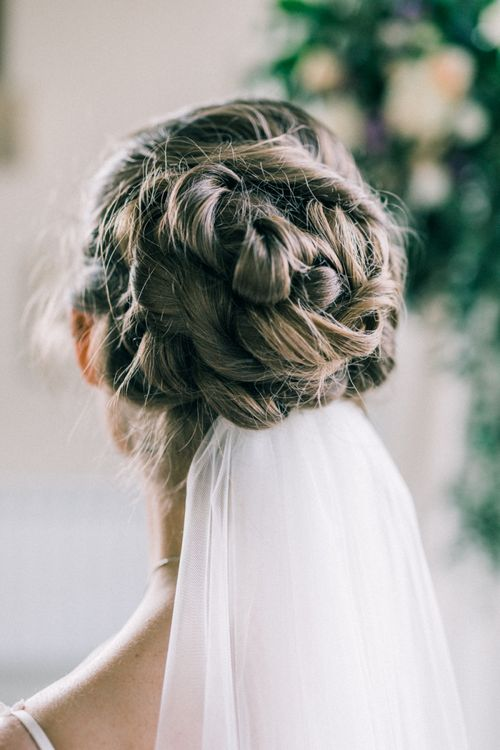 Loose twisted bun with veil pinned at nape of neck