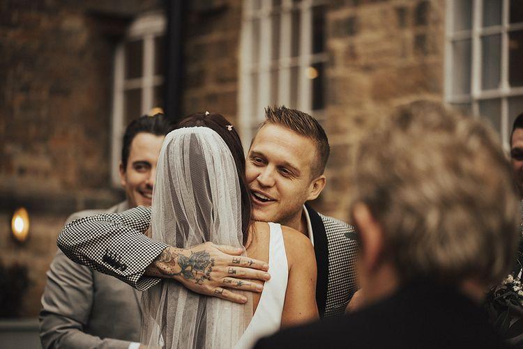 Wedding Guest Hugging Bride in Veil