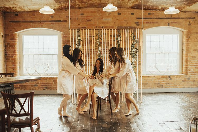 Bridal Party in Silk Getting Ready Robes Enjoying Champagne on the Wedding Morning