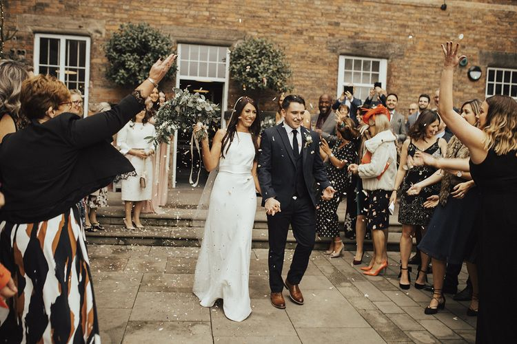 Confetti Exit at The West Mill Industrial Wedding Venue with Bride in Charlie Brear Wedding Dress and Groom in Next Suit