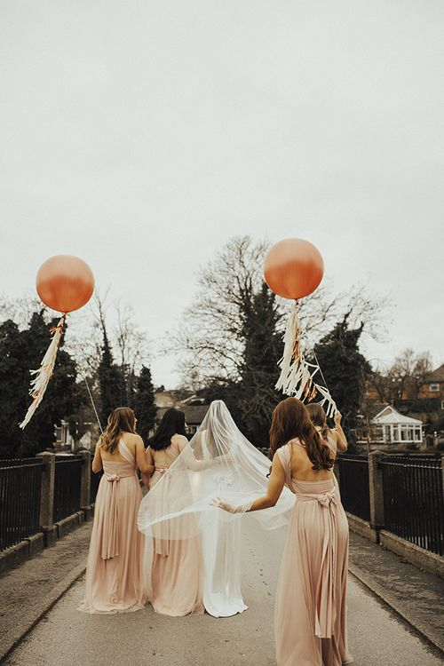 Bridal Party Portrait with Bridesmaids in Pink Victoria Lou Bridal Multiway Dresses with Tulle Holding Giant Balloons with Tassels