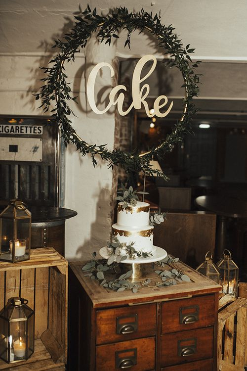 Two Tier Wedding Cake with Foil Decor and Hoop Cake Sign Covered in Foliage