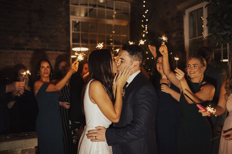 Bride in Charlie Brear Wedding Dress and Groom in Next Suit Kissing During Sparkler Moment