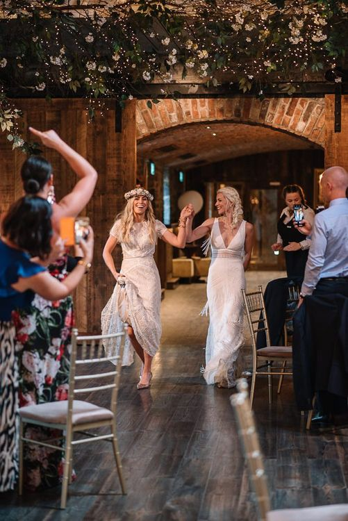 Brides enter wedding reception wearing Watters wedding dress
