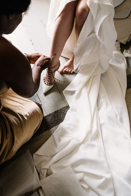 Bride Putting on Her Valentino Rockstud Wedding Shoes
