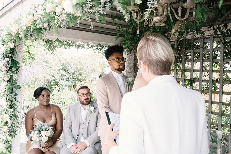 Bride and Groom Exchanging Vows with Their Witnesses Watching Them
