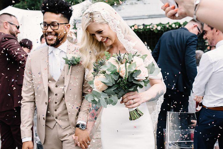 Happy Bride in Pronovias Wedding Dress and Groom in Beige Moss Bros. Suit