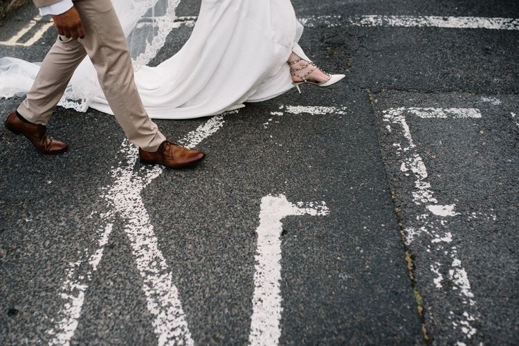 Bride and Groom Walking Across the Road with Bride in Valentino Rockstud Bridal Shoes
