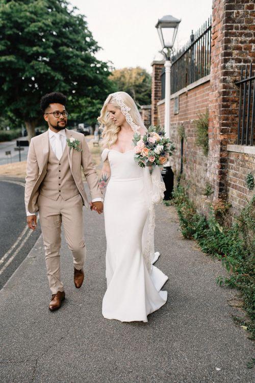 Bride in Pronovias Wedding Dress and Groom in a Beige Moss Bros. Suit