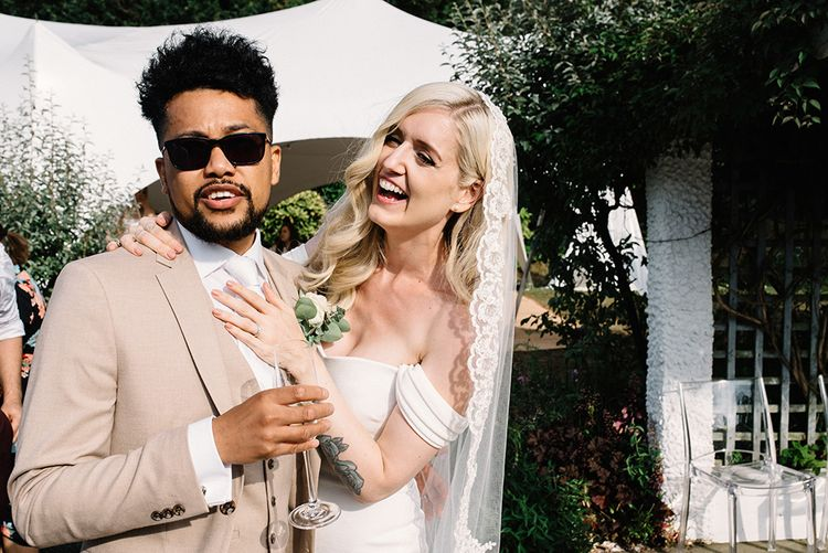 Cool Groom in Sunglasses and Beige Moss Bros. Suit and Bride in Bardot Pronovias Wedding Dress