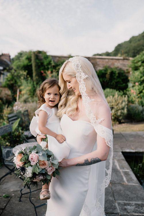 Bride in Bardot Wedding Dress Holding the Flower Girl in Monsoon Dress