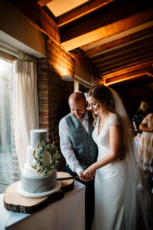 Cutting the Cake | Bride in 'Milan' St Patrick Gown | Groom in Grey Tweed Waistcoat | Intimate Greenery Wedding at Packington Moore Rustic Wedding Venue | Amy Faith Photography | Floodgate Films