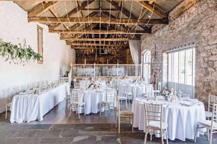 Barn Wedding Reception Decor with Exposed Brick and Fairy Lights Hanging From The Rafters