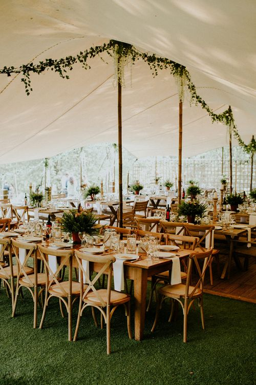 Stretch Tent Wedding Reception with Wooden Tables and Greenery Decor