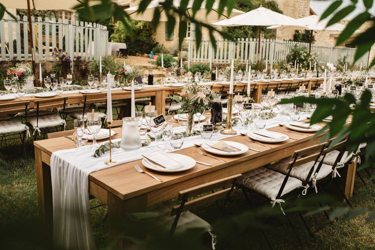 Long Wooden Reception Tables Decorated with Table Runner, Floral Centrepieces and Flowers