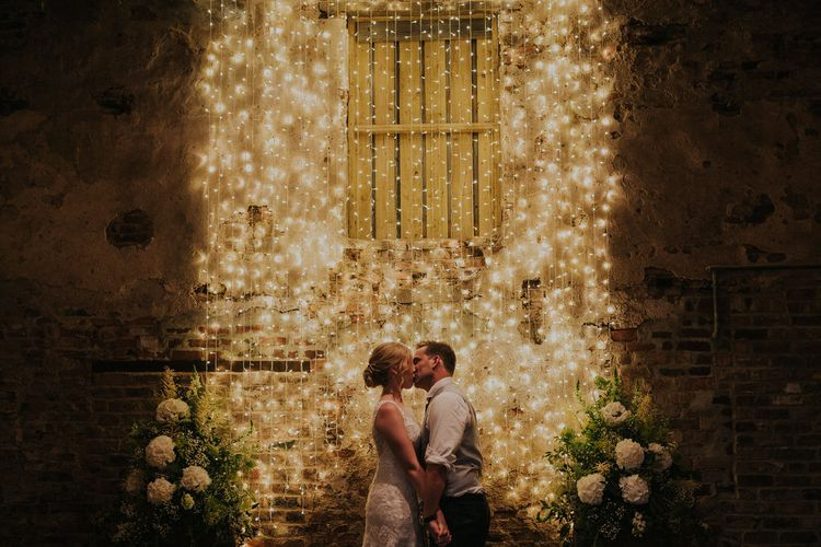 Bride and Groom Kissing in Front of Fairy Light Backdrop