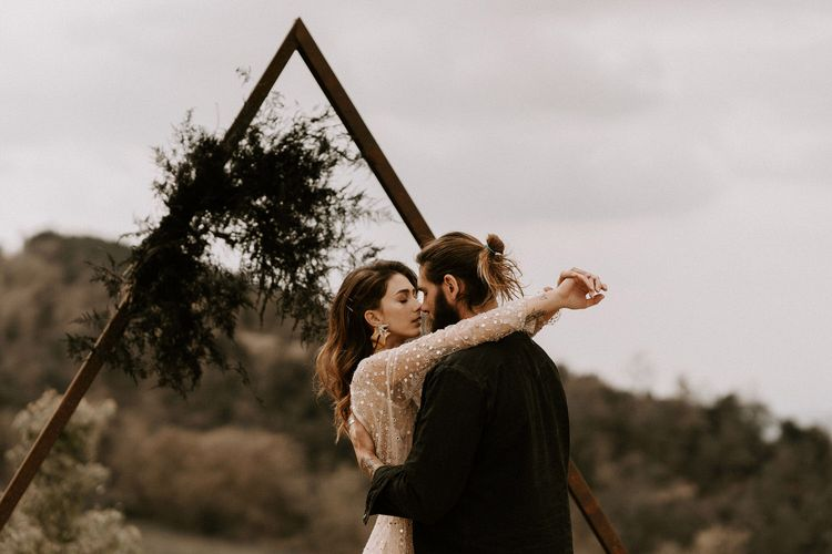 Bride in Gold Shimmering Wedding Dress Embracing Groom in Black Suit with Top Knot