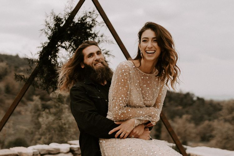 Bearded Groom in Black Outfit Picking Up his Bride in Shimmering Gold Wedding Dress